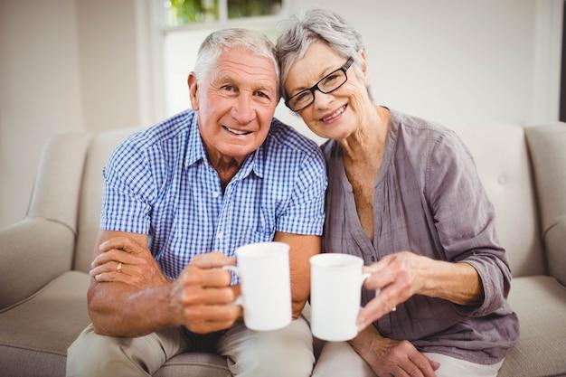 ソファの上に座っているとリビングルームでコーヒーを飲んでいる年配のカップルの肖像画 Premium写真