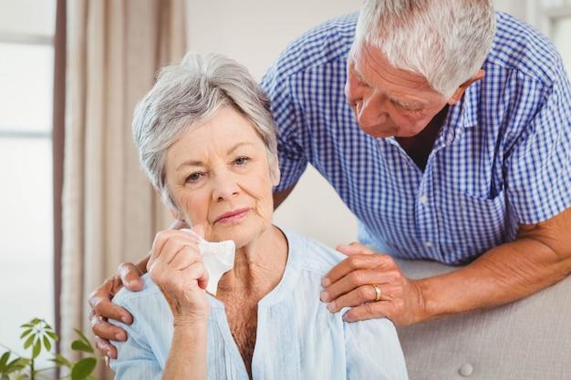 年配の男性がリビングルームで動揺の年配の女性と話しています。 Premium写真