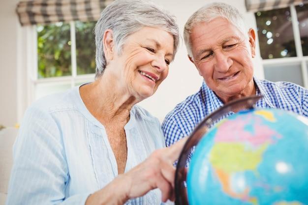 ソファに座っているとリビングルームで地球を見ている年配のカップル Premium写真