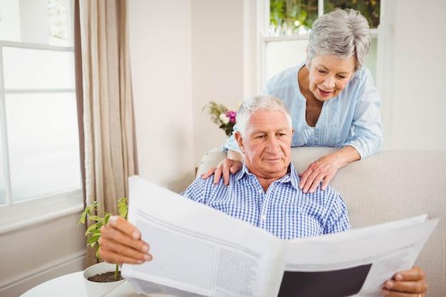 年配の女性がリビングルームで新聞を読んで年配の男性人に話しています。 Premium写真