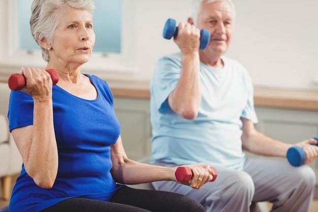 年配のカップルが自宅でエクササイズボールに座りながらダンベルを持ち上げる Premium写真