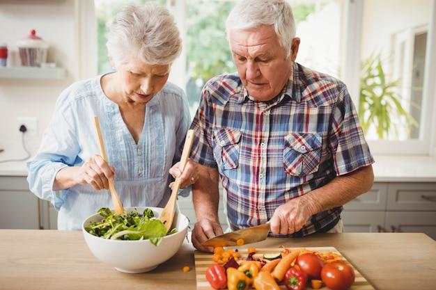 年配のカップルが台所でサラダを準備します。 Premium写真