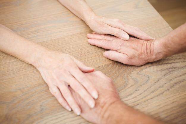 テーブルの上に手を繋いでいる年配のカップル Premium写真
