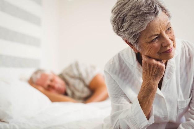 寝室のベッドの上に座って心配している年配の女性 Premium写真