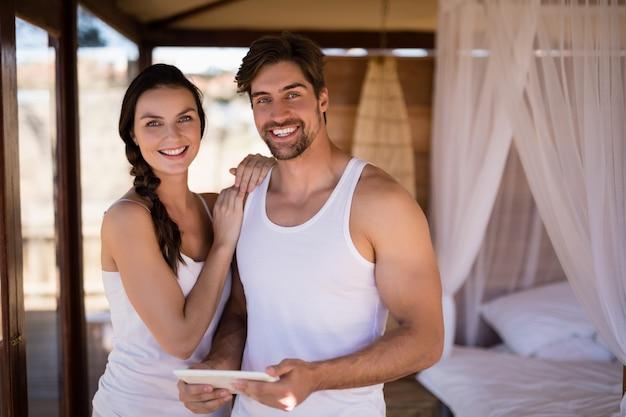 Портрет пары держа цифровую таблетку в коттедже Бесплатные Фотографии