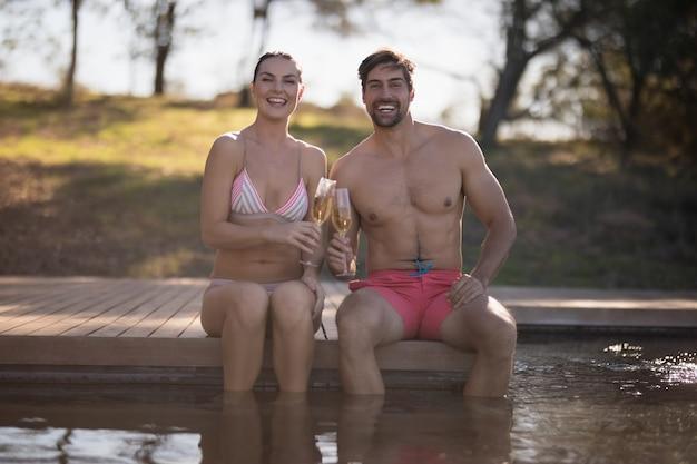 プールでシャンパンのカップル乾杯グラス 無料写真