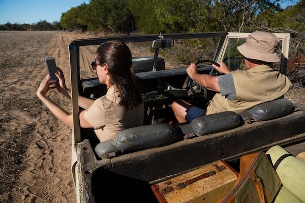 車で旅行中に撮影する男と女 無料写真