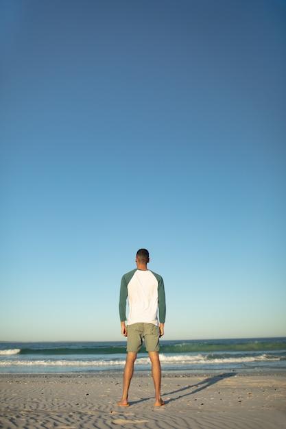 Человек, стоящий на пляже Бесплатные Фотографии