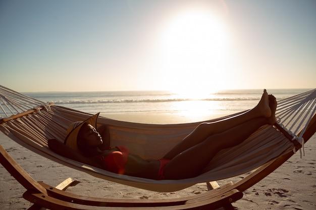 Женщина спит в гамаке на пляже Бесплатные Фотографии