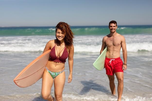 Молодая пара прогулки с доской для серфинга на пляже в лучах солнца Бесплатные Фотографии