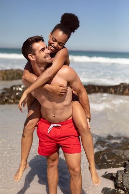 Человек дает контрейлерных женщина на пляже в лучах солнца Бесплатные Фотографии