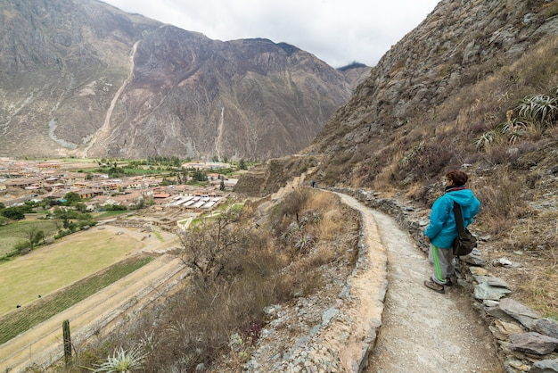 ペルー、クスコ地方の聖地、オリャンタイタンボのインカトレイルと遺跡を探索する旅行者。南アメリカでの休暇と冒険。 Premium写真