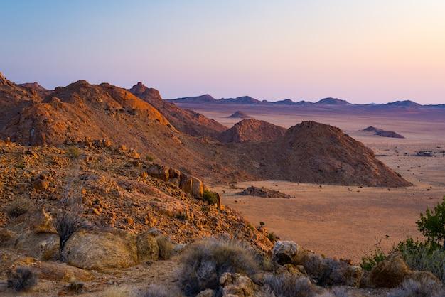 夕暮れ時、ナミブ砂漠、ナミビア、アフリカのカラフルな夕日で岩が多い砂漠 Premium写真