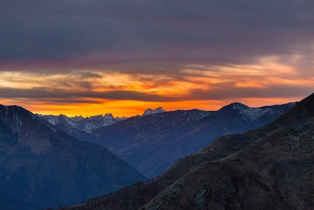 イタリアのフランスアルプスの雄大な山頂の背後にあるカラフルな日光 Premium写真