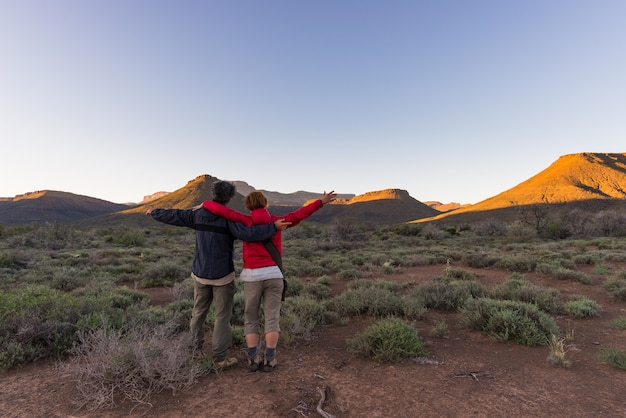 Обниматься пара с вытянутыми руками, наблюдая закат в национальном парке кару на закате Premium Фотографии