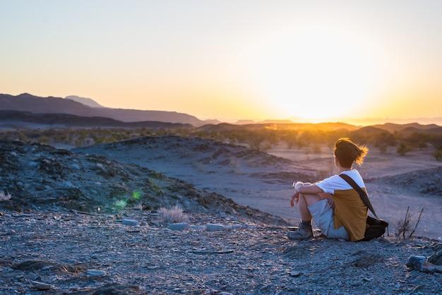 不毛の谷と山々の素晴らしい景色を見ている観光客 Premium写真