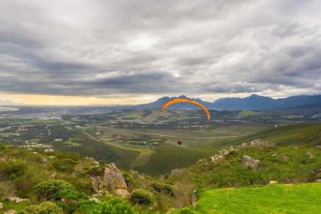 Параплан, летящий над зелеными горами Premium Фотографии