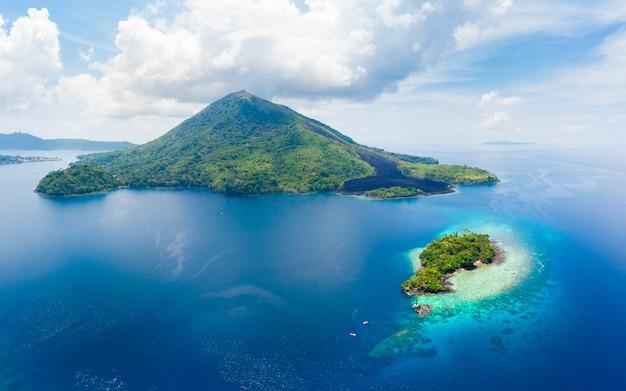 Аэрофотоснимок острова банда молуккский архипелаг индонезия, пулау гунунг апи, лавовые потоки, пляж с белым песком кораллового рифа. лучшее туристическое направление, лучший дайвинг с маской и трубкой. Premium Фотографии