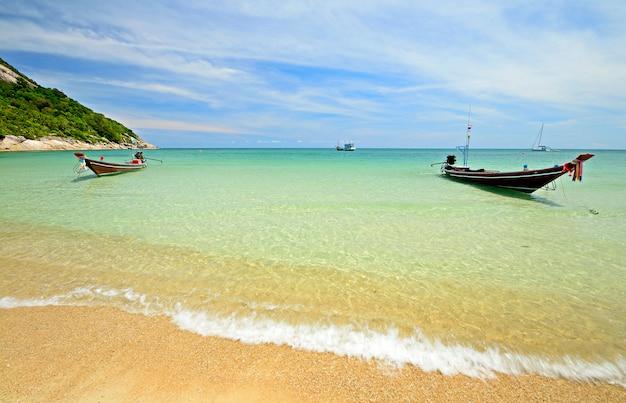 Лодка, плавающая на прозрачной воде, тропический пляж бирюзового моря в таиланде Premium Фотографии