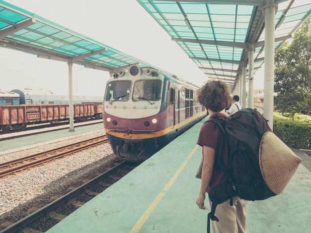 ベトナムの駅でプラットフォーム上の女性バックパッカー待っている電車。休暇中に電車で旅行する一人。世界中をさまよう冒険。 Premium写真