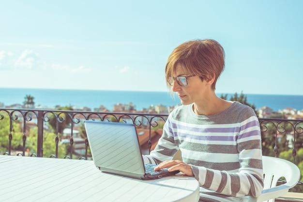 メガネとテラスで屋外のラップトップで働くカジュアルな服装の女性 Premium写真