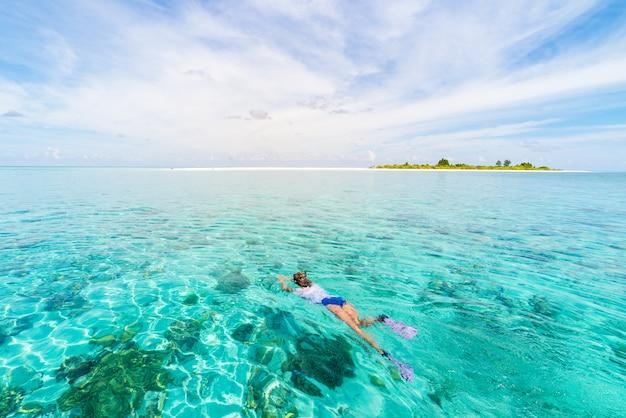 Женщина подводного плавания на коралловом рифе тропического карибского моря, бирюзовая вода Premium Фотографии