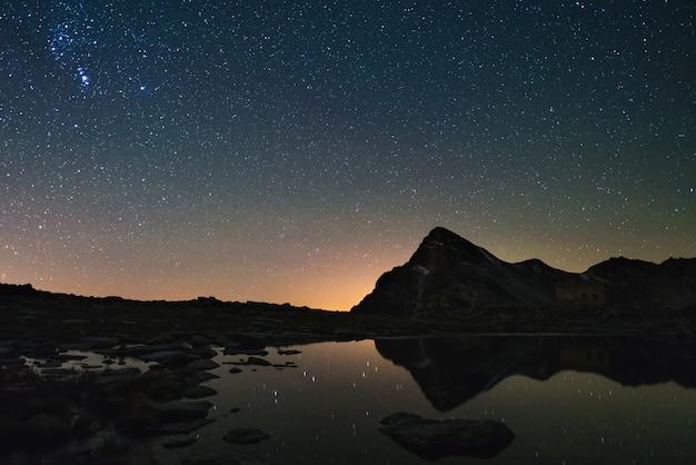 アストロ星空はアルプスの高地で湖に反映されます。輝くオリオン星座。 Premium写真