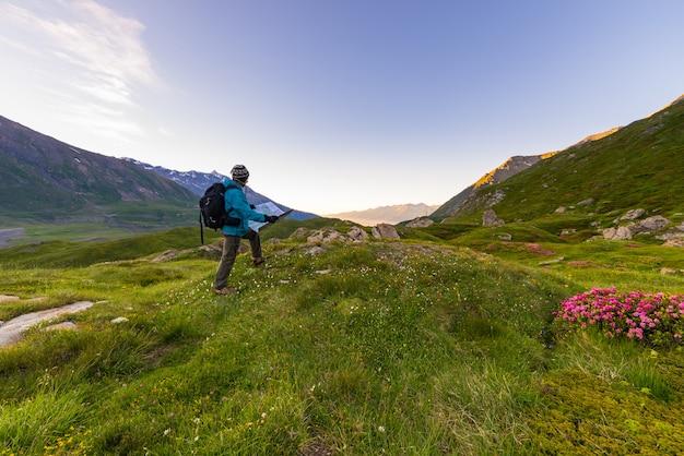 イタリアのフランスアルプスの日の出のトレッキングマップとハイカーバックパッカー。 Premium写真