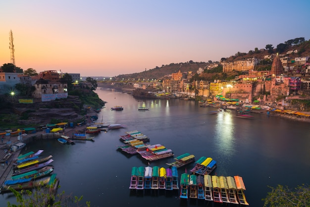 夕暮れ時、インドのオンカレシュワル都市景観。聖なるナルマダ川、浮かぶボート。旅行先。 Premium写真