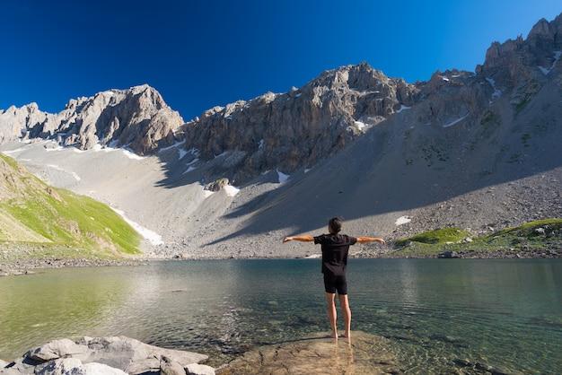 牧歌的な汚染されていない環境で高地の青い湖でリラックスしたハイカーアルプスの夏の冒険。 Premium写真