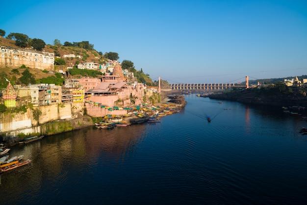 インド、オンカレシュワルの街並み、ヒンドゥー教の神聖な寺院。聖なるナルマダ川、浮かぶボート。 Premium写真