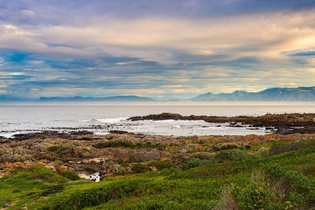 ホエールウォッチングで有名な南アフリカのデケルダースの海の岩の多い海岸線。冬の季節、曇りの劇的な空。 Premium写真