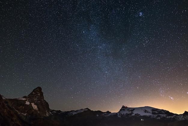 マッターホルン(チェルヴィーノ)山頂とモンテローザ氷河の上の素晴らしい星空。 Premium写真
