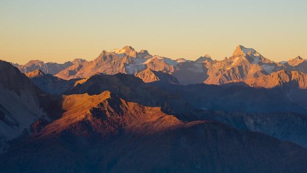 アルプスに沈む夕日。カラフルな空、氷河、マシフデエクラン国立公園、フランスの高山山頂。 Premium写真