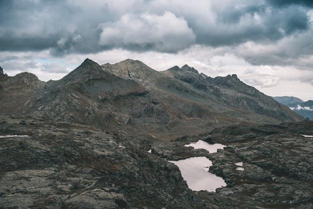 高地の岩の多い風景と小さな湖。劇的な嵐の空と雄大な高山の風景。上から広角ビュー、トーンイメージ、ビンテージフィルター、スプリットトーン。 Premium写真