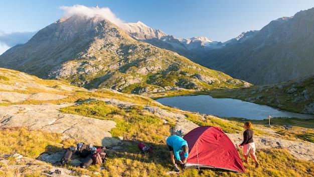 山、時間の経過にキャンプテントを設定する人々のカップル。アルプス、牧歌的な湖、山頂での夏の冒険。 Premium写真