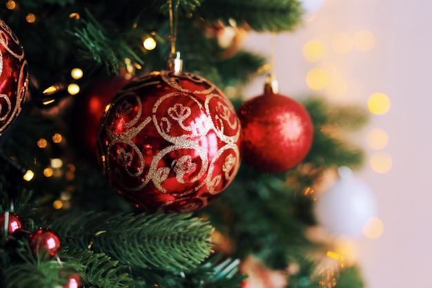 Ярко-красные игрушечные шарики на елке с огнями Premium Фотографии