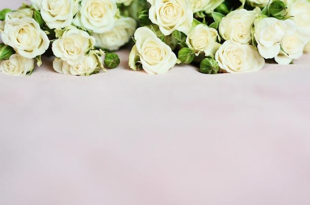 Мягкий розовый фон с маленькими белыми розами для обоев и праздничных открыток Premium Фотографии