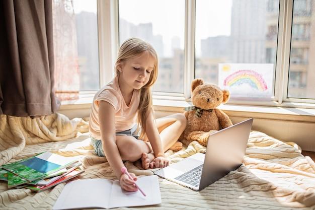 Школьница делает домашнее задание во время онлайн-урока дома Premium Фотографии