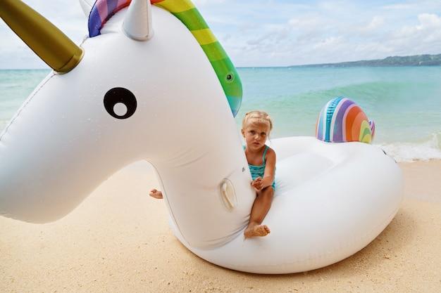 Маленькая девочка на надувном единороге на море Premium Фотографии
