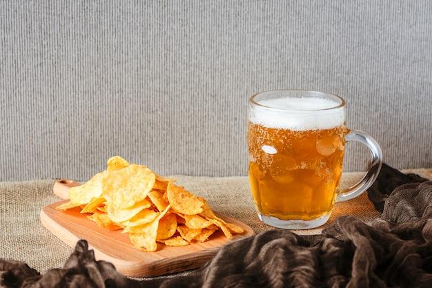 ビールのグラス、ブラウンの塩味のチップス Premium写真
