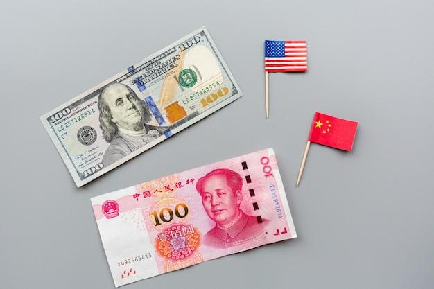 アメリカと中国の国旗と現金のお金のアメリカドルの創造的なトップビューフラットレイアウト Premium写真