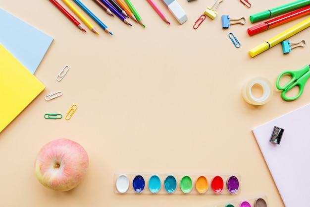 学用品文具、鉛筆、塗料、パステル調のオレンジ色の背景上の紙 Premium写真
