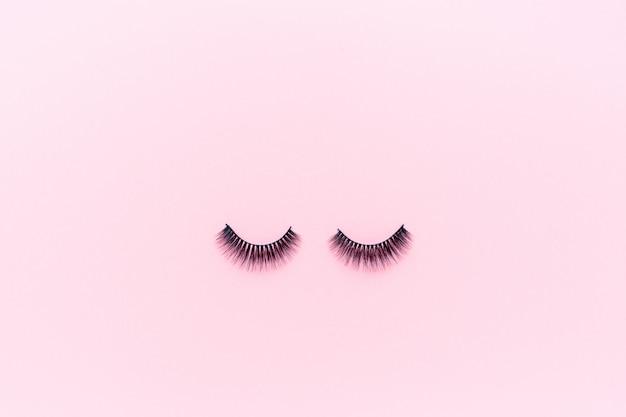 つけまつげはピンクの上に横たわる。 Premium写真