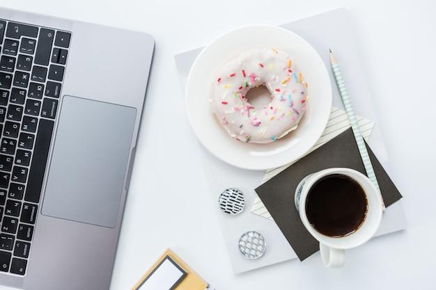 ノートパソコン、鉛筆、ノート、コーヒーカップ、白い背景の上のドーナツとワークスペース。 Premium写真
