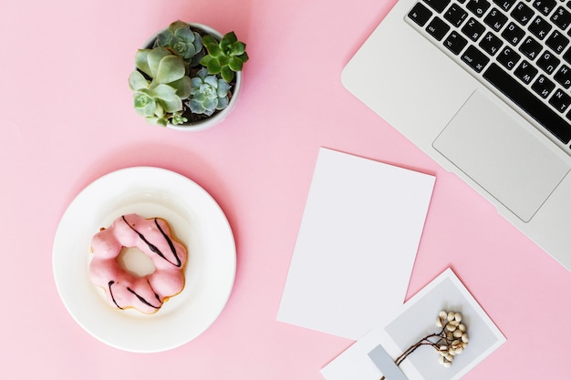 ノートパソコン、多肉植物の花、ドーナツ、テキストの空白の紙とモダンなピンクのオフィスデスクテーブル。 Premium写真