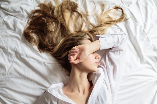 Портрет красивая белокурая женщина спит в постели Premium Фотографии