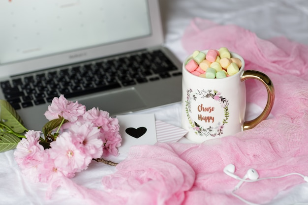 ノートパソコン、ヘッドフォン、マシュマロとコーヒーカップのホームデスク Premium写真