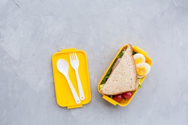 Ланч-бокс с бутербродом и различными продуктами на сером Premium Фотографии