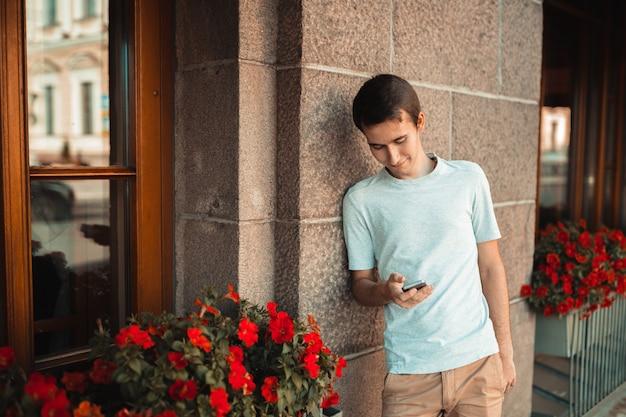 屋外の携帯電話を使用してスタイリッシュな若い男 Premium写真